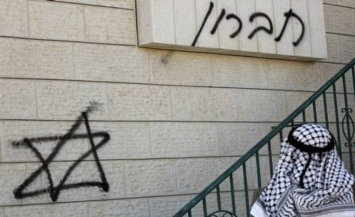 A Palestinian man wearing the traditional chequered head scarf looks on December 2, 2008 at graffitti sprayed at the entrance of a mosque in the West Bank village of Sinjel, near Ramallah, by a group of Israeli settlers earlier in the day. The graffiti in Hebrew reads