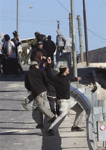Masked Jewish settlers throw stones at Palestinian houses in the West Bank city of Hebron, Tuesday, Dec. 2, 2008. Dozens of Jewish settlers rioted Tuesday in the West Bank town of Hebron, clashing with the Israeli troops who guard them but who may also soon evict them from a disputed building they