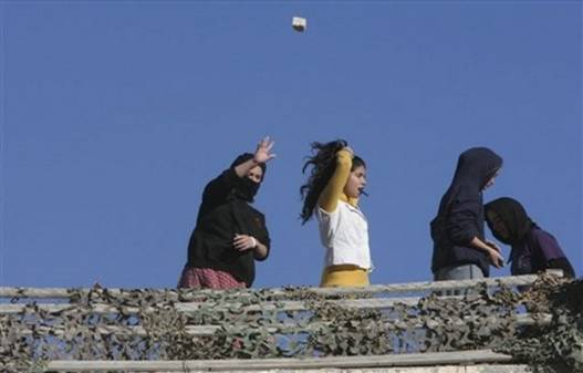 A Jewish settler throws a stone from a rooftop overlooking Palestinian houses in the West Bank city of Hebron, Tuesday, Dec. 2, 2008. Dozens of Jewish settlers rioted Tuesday in the West Bank town of Hebron, clashing with the Israeli troops who guard them but who may also soon evict them from a disputed building they