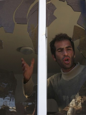 A Palestinian man shouts as he stands near a window shattered after Jewish settlers threw stones at it in the West Bank city of Hebron December 2, 2008. Jewish settlers and Palestinians threw stones in clashes on Monday that injured five in Hebron where Jews want to stop the eviction of 13 settler families, witnesses said. From Reuters Pictures by REUTERS.
