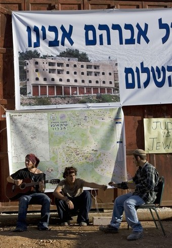 Jewish settlers play guitar in front of a disputed house occupied by settlers in the divided West Bank city of Hebron on November 23, 2008. About 100 Jewish settlers last week defied a High Court order to evacuate the house in the flashpoint West Bank city of Hebron, and braced for possible confrontation with police. The court rejected an appeal by two rightwing organisations against an order issued by the state to evacuate the Hebron house, which the settlers claim they had purchased from a Palestinian, who denies selling the house. The controversial house was occupied by dozens of hardline Jewish settlers in March 2007. They have remained in the four-storey building which they dubbed