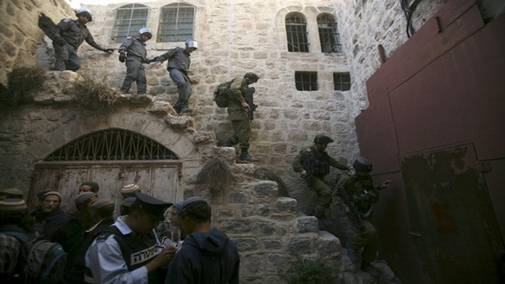 Israeli soldiers and police officers walk down the stairs after removing Jewish settlers from a previously evacuated house in the West Bank city of Hebron December 3, 2008. According to local media reports, dozens of Jewish settlers were removed by Israeli police on Wednesday from a house that had been evicted in 2006 following a High court order. From Reuters Pictures by REUTERS.