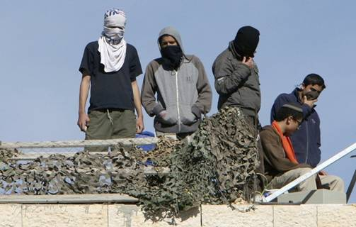 Masked Jewish settlers stand atop the roof of a disputed building, occupied by settlers in March 2007, in the West Bank city of Hebron, December 3, 2008. Hardline Jewish settlers have vowed to resist an Israeli court order to leave the building they insist they bought from a Palestinian. Hundreds of settler supporters, mostly youths, have come to the Jewish enclave in the past week to try to prevent the evacuation of the building, raising tensions. Palestinian Faiz Rajabi said the building belongs to him and he has denied selling it to the settlers. From Reuters Pictures by REUTERS.